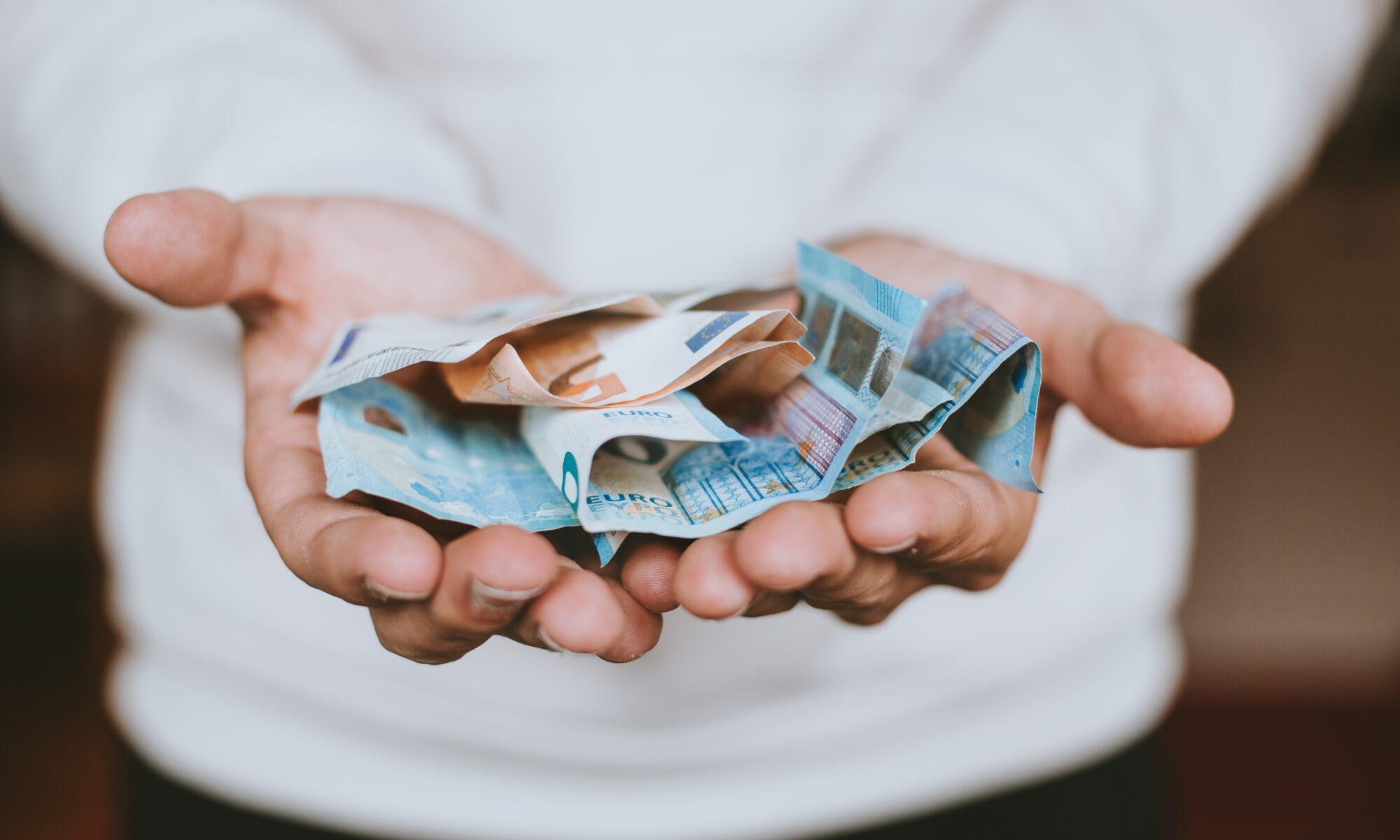 Geldscheine in ausgebreiteten Händen